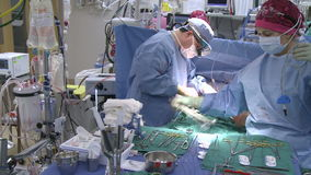 Pan left to right of open heart surgery (1 of 2). Scene from a typical hospital stock video