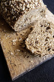 Pan marrón del trigo integral griego en el tablero de pan Foto de archivo