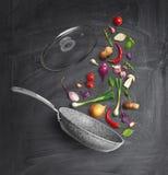 pan met een deksel en vliegende groenten, op een schoolraad royalty-vrije stock foto