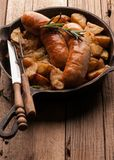 Pan mit gebratenen Kartoffeln und gegrillte Würste, grüner Rosmarin, Gabel und Messer stockfotografie