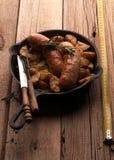 Pan mit gebratenen Kartoffeln und gegrillten Würsten stockbilder