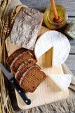 Pan negro con queso del brie en una tabla de cortar Imagenes de archivo