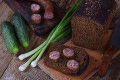 Pan negro del corte fresco con la salchicha hecha en casa, las cebollas verdes y los pepinos en un fondo rústico de madera Bocado Fotos de archivo
