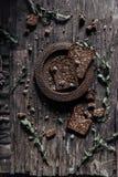 Pan negro del salvado en la tabla de madera Imagenes de archivo