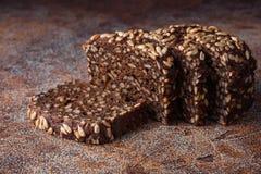 Pan negro fresco con las semillas de girasol en una tabla oxidada vieja Foto de archivo