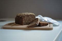 Pan oscuro con las semillas en la tabla blanca imágenes de archivo libres de regalías
