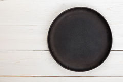 Pan for pizza space for text. Empty round cast-iron frying pan for pizza or pie on a white wooden background, space for text stock image