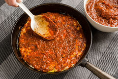 Pan pizza. White ladle spreading tomato sauce on pizza dough in cast iron frying pan stock photos