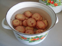 Pan of potatoes. White pan with picture of vegetables, full of water and potatoes Stock Images