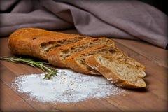 Pan quebradizo de Rye con la harina en la tabla de madera Imagen de archivo