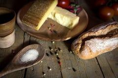 Pan, queso y sal rústicos en una tabla de madera Imágenes de archivo libres de regalías