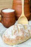 Pan rústico fresco con la taza de leche y de cuchara de madera Fotografía de archivo libre de regalías