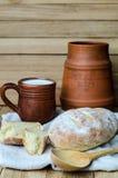 Pan rústico fresco con la taza de leche y de jarro Foto de archivo libre de regalías