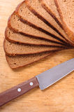 Pan rebanado en una tarjeta y un cuchillo de madera de corte Imagen de archivo