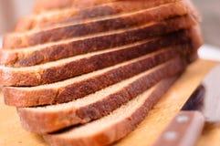 Pan rebanado en una tarjeta y un cuchillo de madera de corte fotografía de archivo