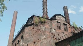 Pan of red brick wall of abandoned metallurgic plant with three chimneys. stock footage
