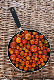 Pan of Red Ripe Whole Tomatoes. Red Ripe Tomatoes in Frying Pan on Wicker Picnic Basket royalty free stock photo