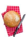Pan redondo con el cuchillo en servilleta checkered Imagen de archivo