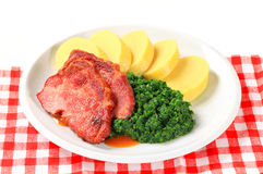 Smoked pork neck with potato dumplings and spinach Royalty Free Stock Images