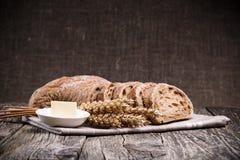 Pan sabroso con trigo en fondo de madera Fotos de archivo