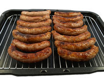 A pan of sausages. A grill pan of cooked pork sausages - isolated on white royalty free stock images