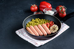 Pan with sausages and vegetables Tasty dinner Place for text Royalty Free Stock Photography
