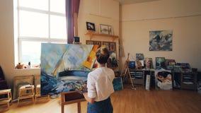 Pan schoss vom weiblichen Maler, der Marinelandschaft auf Segeltuch unter Verwendung der Ölfarben, der Bürste und der Palettenfun stock footage