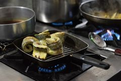 Pan sear sword fish on a hot pan with gas burner flame Royalty Free Stock Image