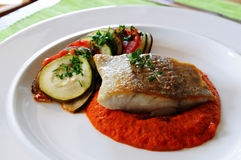 Pan seared black cod. Pan seared black cod with spicy vegetable sauce and roasted vegetables - ratatouille style stock photo