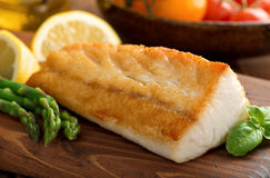 Pan Seared Fish. A delicious pan seared white fish with asparagus, salad, and lemon Royalty Free Stock Images
