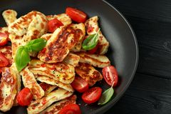 Pan-seared halloumi cheese and sweet cherry tomatoes salad.  royalty free stock photography