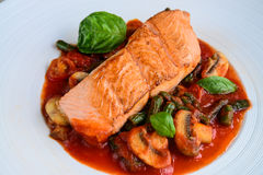 Pan seared salmon with mushrooms in basil tomato broth Royalty Free Stock Photo
