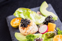 Pan seared scallops with salad, avocado, radish, mango and black Royalty Free Stock Photo