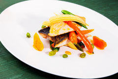 Pan seared sea bass served with vegetables Stock Photography