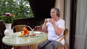 Senior woman with her coffee on terrace in summertime stock video