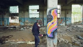 Pan shot of adult man graffiti artist in protective face mask and gloves painting on high pillar inside damaged empty. Industrial building. Creativity and young stock footage