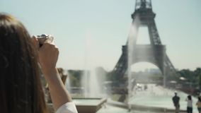 Pan shot back of elegant woman making photo of Eiffel Tower with film camera. Pan shot back of elegant woman dressed in white shirt and black skirt making photo stock video