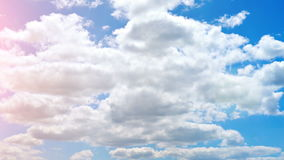 Pan shot of blue sky with clouds and bright sun. Panoramic shot of summer sky. Blue daylight summer sky with fluffy stock footage