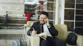 Pan shot of cheerful confident businessman talking mobile phone smiling and writing notes in notepad while sits on stock footage