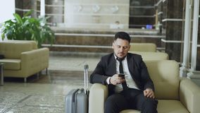 Pan shot of concentrated businessman using smartphone sitting on armchair inside luxury hotel with luggage near him. Pan shot of concentrated businessman using stock footage