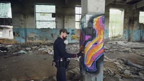 Pan shot of damaged abandoned building with high columns inside and male graffiti artist drawing abstract images on. Pan shot of damaged abandoned building with stock video