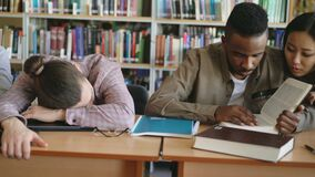 Pan shot of diligent students preparing for exams doing homework and tired guy sleeping on table in college library. Indoors stock footage