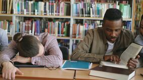 Pan shot of diligent students preparing for exams doing homework and tired guy sleeping on table in college library. Indoors stock video