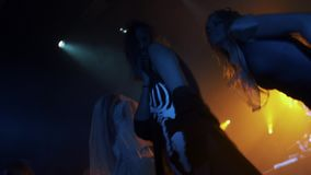 Pan shot of girls in halloween costumes dancing on scene at night club party. Panoramic shot of girls in halloween costumes and face paint dancing on scene at stock video