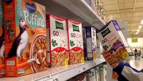 Pan shot of man selecting cereal in grocery store