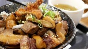 Pan shot of people eating beef mushroom donburi on table stock video footage