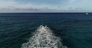 Slow motion, Aerial point of view, life guard on jet ski performing rescue operation off the coast of, Honolulu, Hawaii, in deep b