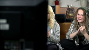 Pan shot of two girls watching television smiling and clapping stock video