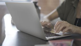 Pan shot up of woman s hands typing and using touchpad. Close up of woman s hands typing at her laptop keyboard and using a touchpad in an office. Left to right stock footage