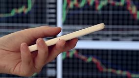 Pan shot of woman checking smart phone stock information. With stock market background stock video footage